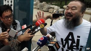 Activist artist Ai Weiwei gestures while speaking to journalists gathered outside his home in Beijing, China on Thursday