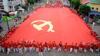 Residents of Chongqing, China, hold a giant Communist Party flag ahead of the 90th anniversary of the founding of the Communist Party next month