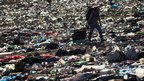 A festival-goer walks through rubbish left behind at the end of  the Glastonbury music festival in southern England