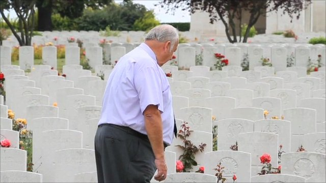 A man standing with white headstones