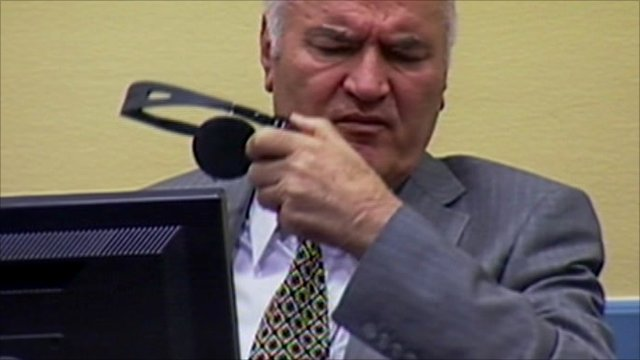 Ratko Mladic removes his headphones in court