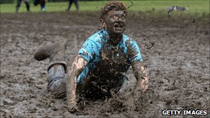 Tom Wilder, 17, from Kent, dives in the mud at the Glastonbury Festival on 23 June 2011