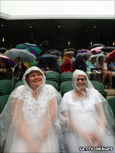 Fans wear rain gear before the cover goes on centre court as rain delays play on day eight of the Wimbledon Lawn Tennis Championships