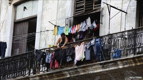 A woman hangs her laundry from the balcony of her colonial-era apartment in Havana 3 July,  2011