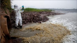 A Greenpeace campaigner takes a sample of yellow-coloured waste water from the discharge pipe at the Youngor Textiles Factory