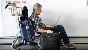 Man uses laptop at airport
