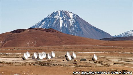 14 ALMA antennas on the Chajnantor plateau. In the background, the 5300m Cerro Chico is towered over by the 5,920m Licancabur volcano. May 2011.