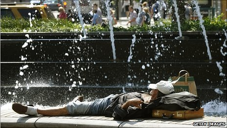 A man laying in front of a fountain