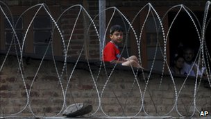 A Kashmiri boy looks through barbed wire set up by Indian policemen in Srinagar, India, on 13 July 2011 after separatists protesting against Indian rule declared a strike