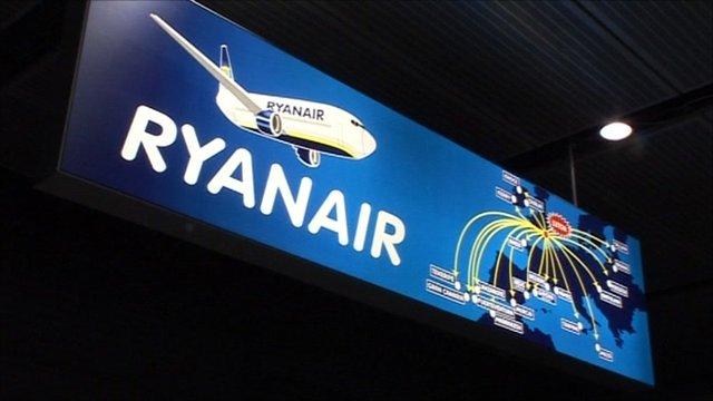 A lit billboard advertising Ryanair at London Luton Airport