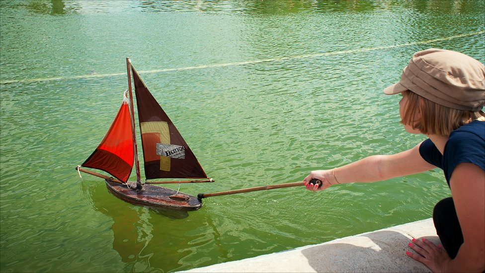 A young girl launching a rented model sailboat in the Jardin des Tuileries, Paris, France