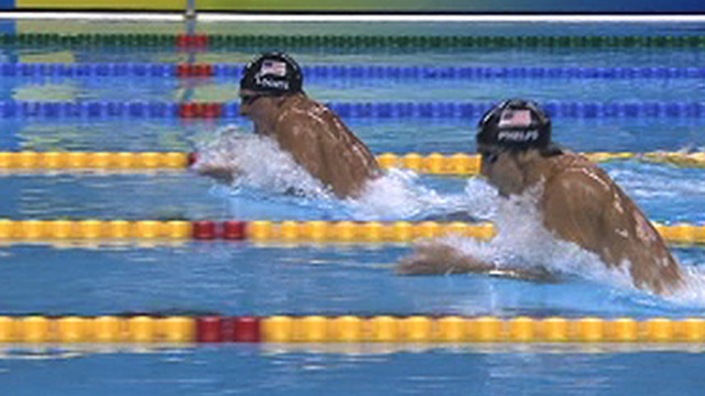 American Ryan Lochte breaks the world record on his way to beating country-man Michael Phelps