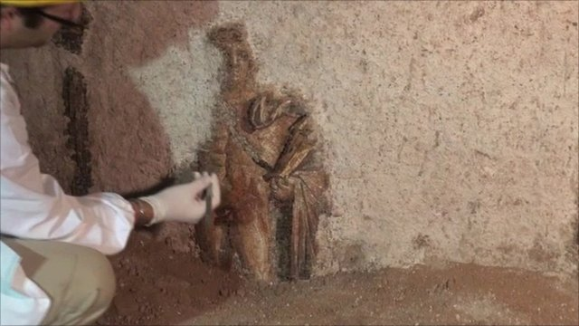 Archaeologist brushing dust from mosaic of Apollo