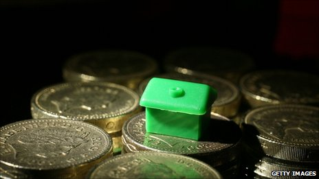 A Monopoly house on top of a pile of pound coins