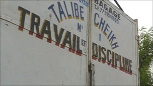 The Mouride motto 'Work and Discipline' painted on the back of a lorry