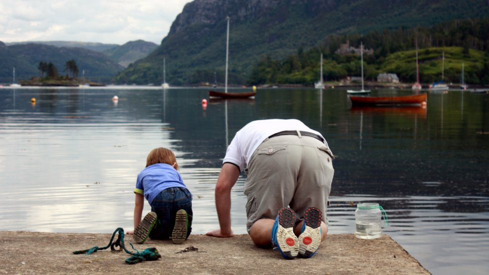 Man and boy peering over the edge of the pier in Plockton
