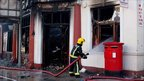 A firefighter sprays water into a burnt-out pub in Tottenham, north London.