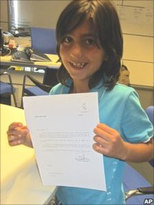 In this undated photo released by the Coira family, Leonel Angel Coira shows the contract he signed with Real Madrid at their headquarters in Madrid, Spain
