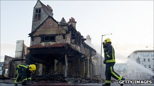 Firemen douse the charred remains of the House of Reeves furniture store in Croydon
