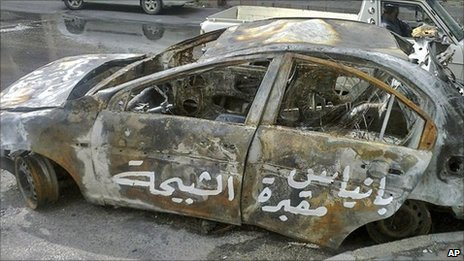 """Arabic graffiti on a burnt-out car reads: """"Baniyas is the grave of the shabiha."""""""