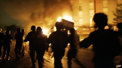 In this Nov. 3, 2005 file photo, French Riot police officers run past a burning car in Paris suburb, Aulnay-sous-Bois on the seventh day of unrest.