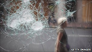 A woman walks past a broken cafe window in Clapham Junction on August 10, 2011 in London, England.