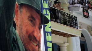 People look from a Havana balcony beside a giant poster of Fidel Castro