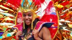 Dancer smiles for the camera as she takes part in Nottingham's Caribbean carnival parade through the city streets to the Forest Recreation Ground on 14 August 2011