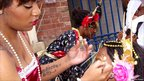 Woman applies make-up to a performer before the Nottingham Caribbean Carnival parade from the city centre to the Forest Recreation Ground on 14 August 2011