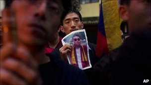 A Tibetan exile holds a portrait of Tsewang Norbu, during a candle light vigil in Dharmsala, India, Monday, Aug. 15, 2011