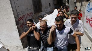 Palestinians carry the body of a dead tunnel worker in a Rafah funeral procession.