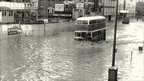 A bus driving through floodwater on Great Victoria Street, Belfast