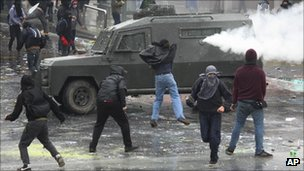 Protesters throw stones at an armoured police vehicle spraying tear gas during the second day of a national strike in Santiago, Chile, on Thursday