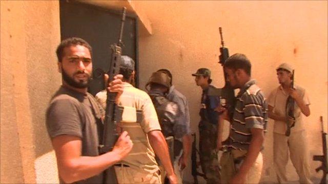 Rebel fighters enter a building