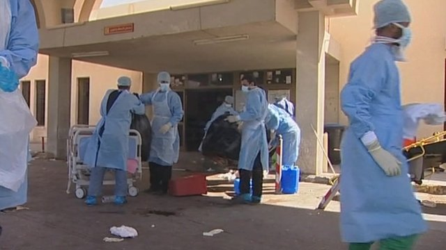 People wearing medical clothes clearing bodies from hospital