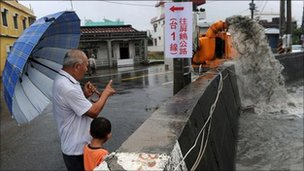 """A man shows his grandson a water pump (R) extracting overflowing water caused by rain brought by Typhoon Nanmadol in Linbian in Taiwan""""s southern Pingtung county on August 29, 2011."""