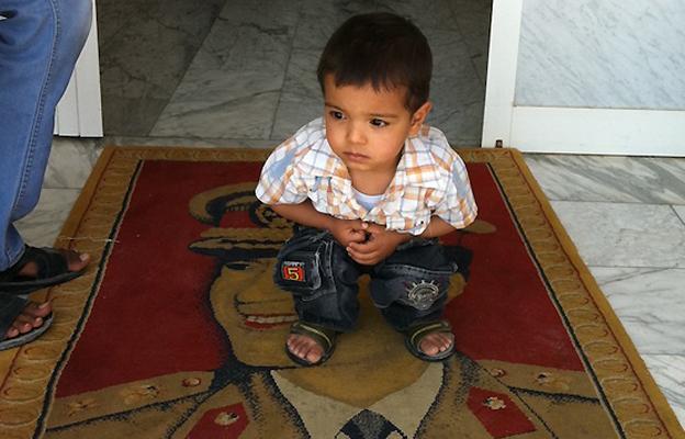 Boy squatting on Gaddafi image, 5 July
