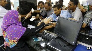 People rush to get cash from their accounts after the Libyan banks reopen