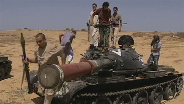 Anti-Gaddafi forces standing on a tank