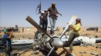 Anti-Gaddafi fighters stand on the propeller of a damaged plane outside the military base of Libya's Khamis Brigades, 7 September 2011