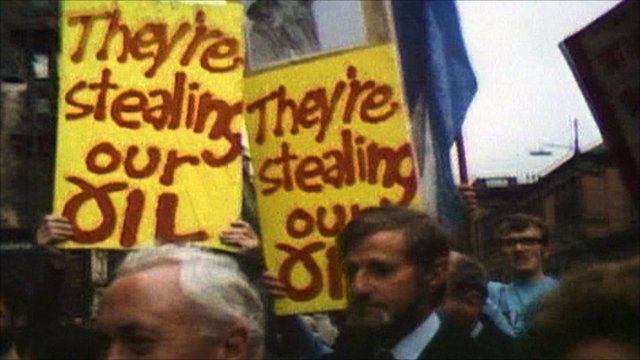 Protestors carry placards as Harold Wilson walks past