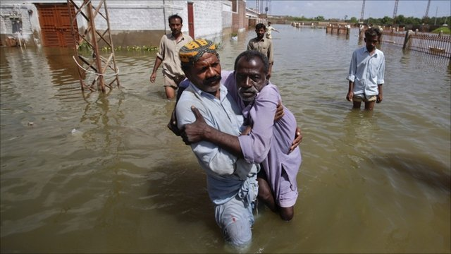 Residents assist a handicapped man while escaping to higher ground from their flooded village in the Mirpur Khas