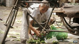 An elderly man scavenges discarded produce at a vegetable market in Beijing.