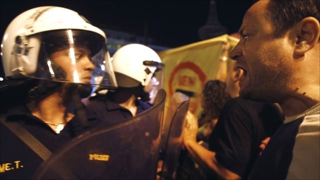 An anti-austerity protester shouts at police officers outside the Greek parliament