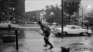 Police take cover behind parked cars in Newark in July, 1967
