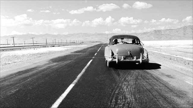 single car on desert highway in 1950's