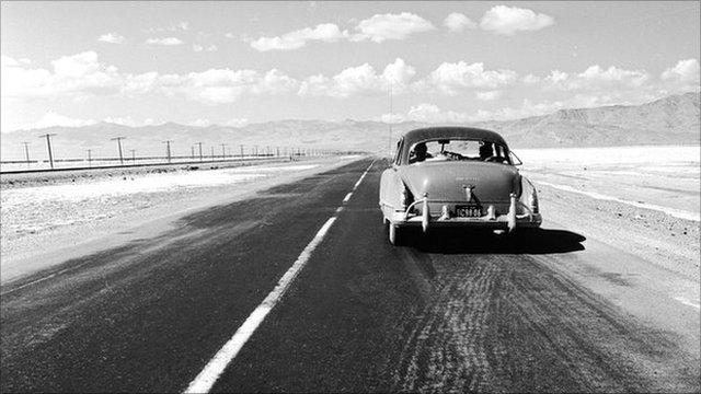 single car on desert highway in 1950's