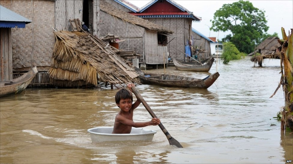 A young boy rows through water in Kandal province, Cambodia, on 3 October  2011
