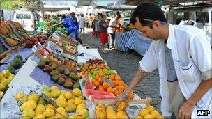 A fruit stall owner arranges his goods in a Rio de Janeiro market