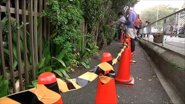A row of cones and tape in front of the fence where radiation was found